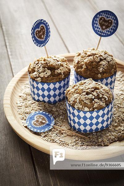 Teller mit drei Eichenflocken Muffins auf Holz