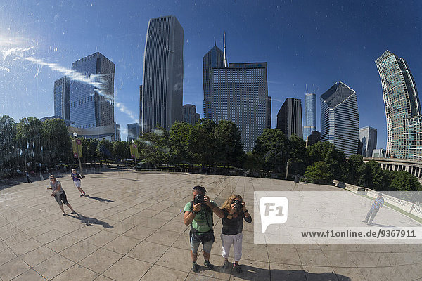 USA,  Illinois,  Chicago,  reflection of two photographers standing in front of Cloud Gate on AT and T Plaza taking a picture