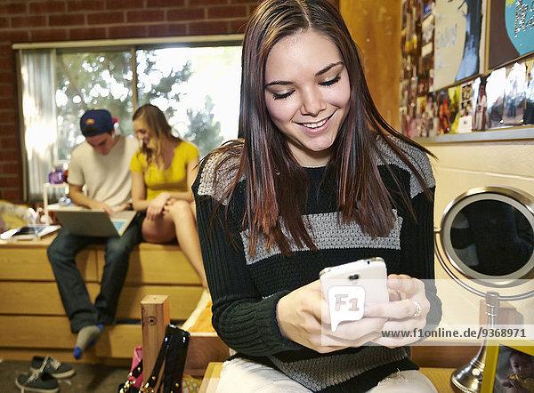 Handy benutzen Europäer Zimmer Student Schlafsaal