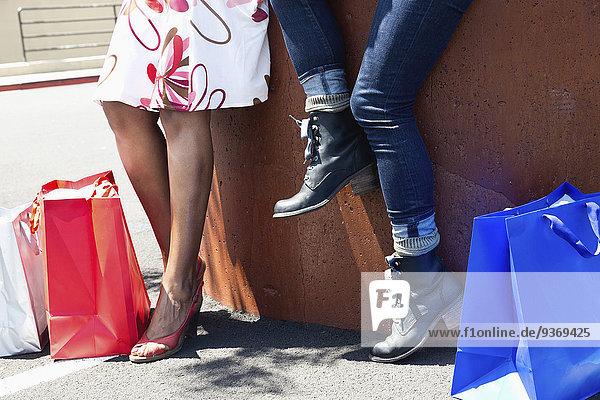 Außenaufnahme sitzend Frau Tasche kaufen freie Natur