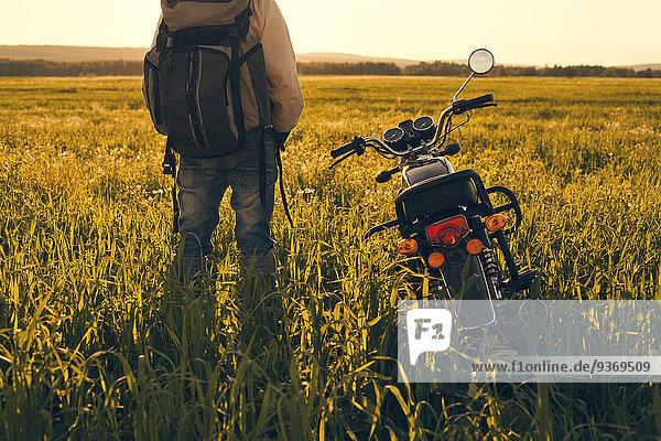 stehend Mann Feld Motorrad
