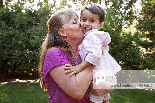 Grandmother kissing grandson in backyard