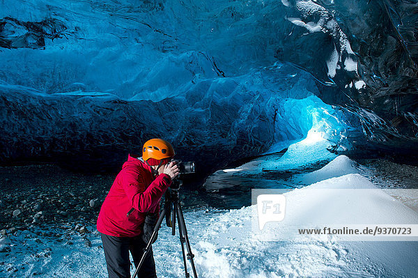 Photographer taking photograph in ice cave