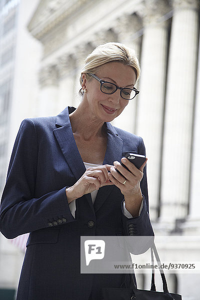Caucasian businesswoman using cell phone in city street  New York City  New York  United States