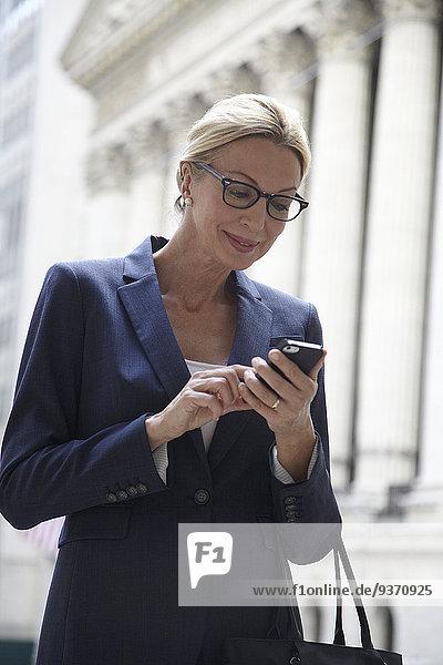 Handy benutzen Europäer Geschäftsfrau Vereinigte Staaten von Amerika USA New York City Straße Großstadt