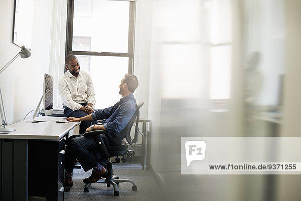 Büroalltag. Ein Mann lehnt sich in einem Bürostuhl zurück und unterhält sich mit einem Kollegen  der auf der Schreibtischkante sitzt.