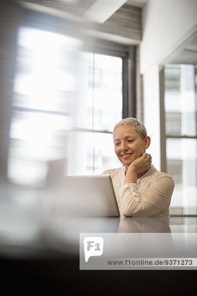 Büroalltag. Eine Frau sitzt mit einem Laptop-Computer.