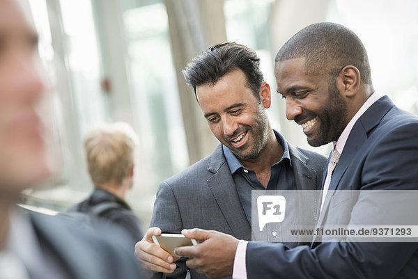 Zwei Männer überprüfen ein Smartphone.