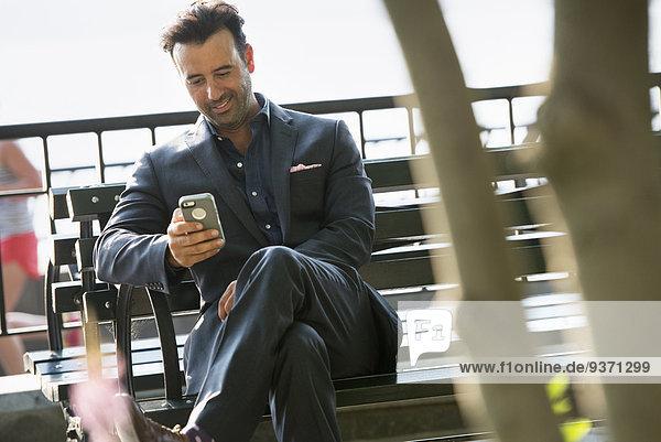Ein Geschäftsmann sitzt und schaut lachend auf sein Telefon.