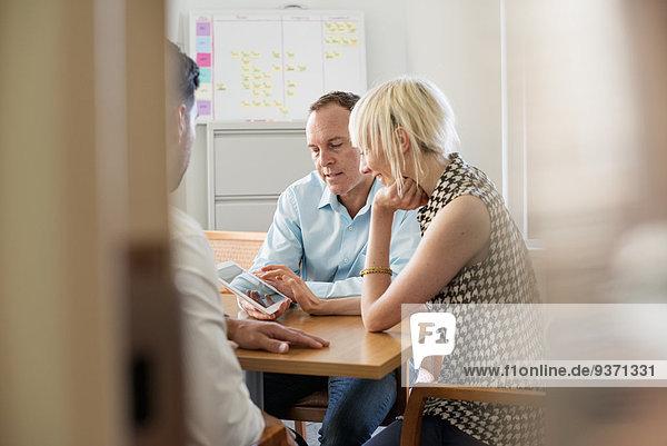 Drei Geschäftskollegen in einem Büro  die sich an einem Tisch unterhalten und auf ein digitales Tablet schauen.