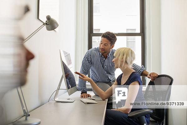 Drei Geschäftskollegen in einem Büro  zwei sprechen und einer steht an der Tür.