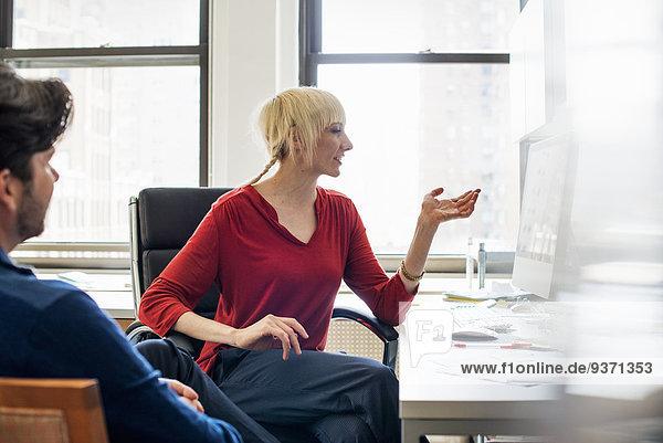 Büroalltag. Ein Mann und eine Frau in einem Büro  im Gespräch miteinander sitzend.