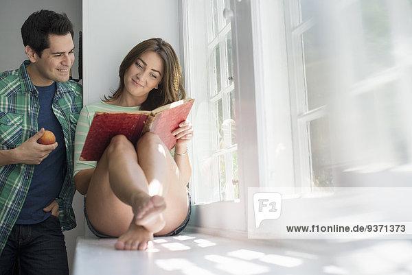 Eine Frau sitzt am Fenster und liest ein Buch. Ein Mann steht neben ihr und isst einen Apfel.