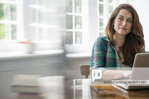 Lächelnde Frau mit Laptop im Heimbüro.