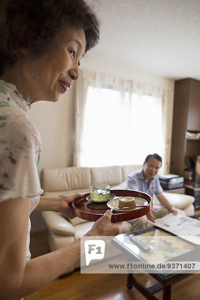 Eine Frau serviert einem Mann  der auf einem Sofa sitzt  ein Tablett mit Essen.