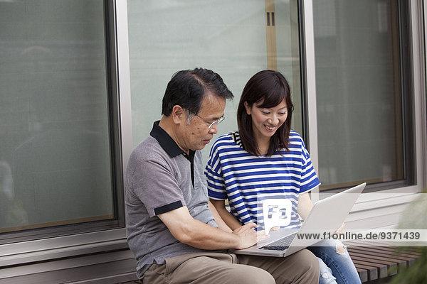Ein Mann und eine Frau sitzen vor einem Haus. Sie halten einen Laptop-Computer in der Hand.
