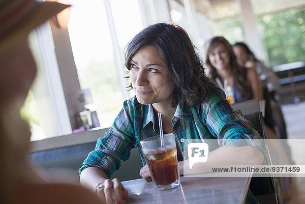 Eine Frau  die an einem Diner sitzt und aus dem Fenster schaut. Ein kühles Longdrink mit einem Strohhalm.