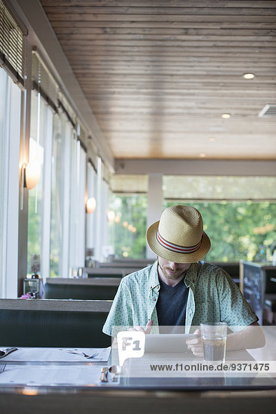 A man wearing a hat sitting in a diner using a digital tablet.