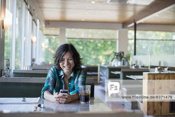 sitzend Frau sehen lachen Hemd Smartphone Tisch