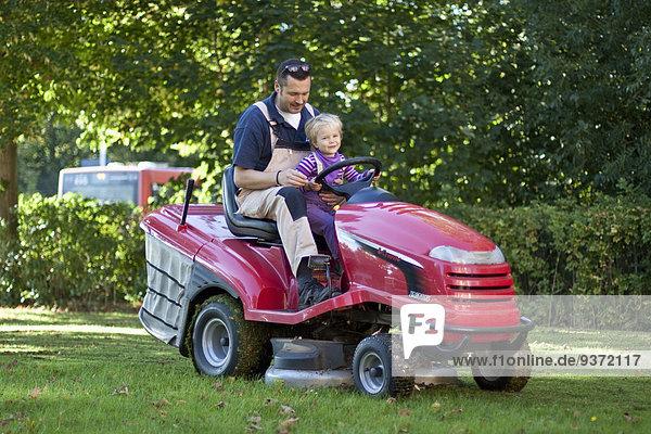 Vater und Tochter auf einem Rasenmäher