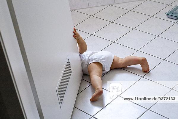 Baby spielt mit Badezimmertür Baby spielt mit Badezimmertür