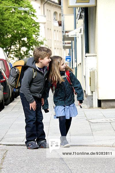 Two children walking to school  keeping an eye on the traffic  Munich  Bavaria  Germany