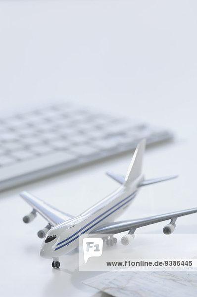 Flugzeugmodell  Tastatur und Landkarte auf Schreibtisch