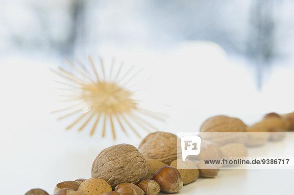 Verschiedene Nüsse und Strohstern