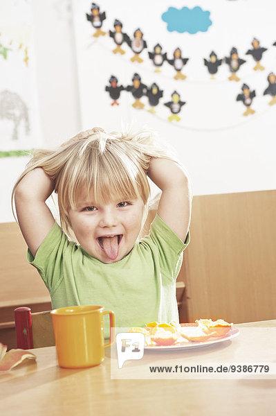 Girl At Table Sticking Out Tongue  Kottgeisering  Bavaria  Germany  Europe