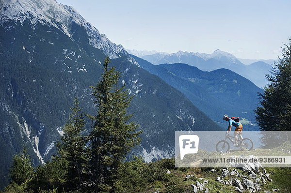 Mountain biker looking at Alpine scenery  Tyrol  Austria