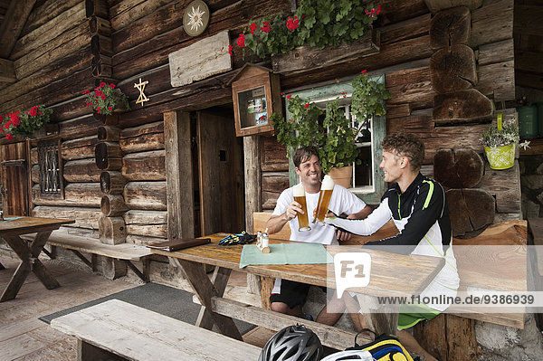 Two men drinking beer together  Hornbacher Alm  Chiemgau  Germany