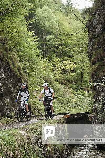 Two mountain bikers riding on a trail  Schwarzachental  Bavaria  Germany