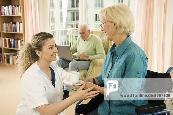 Senior Senioren Frau empfangen Wohnhaus Sorge Tee