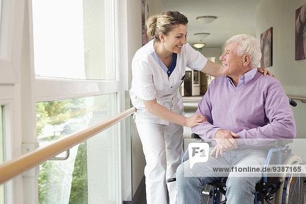 Senior Senioren Mann sprechen Rollstuhl
