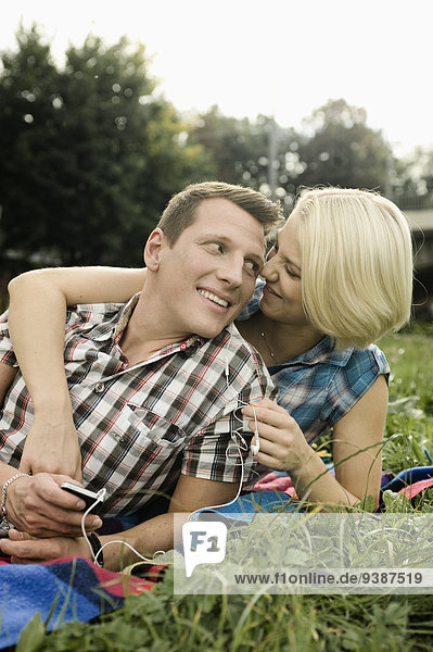 Young couple listening to music in a park  Munich  Bavaria  Germany