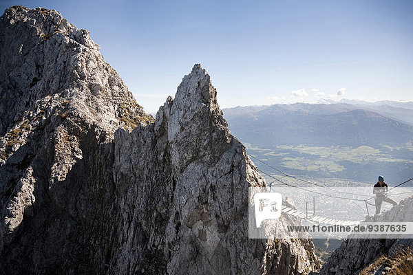 Female alpinist rock climbing  standing on bridge  Innsbruck route  Tyrol  Austria