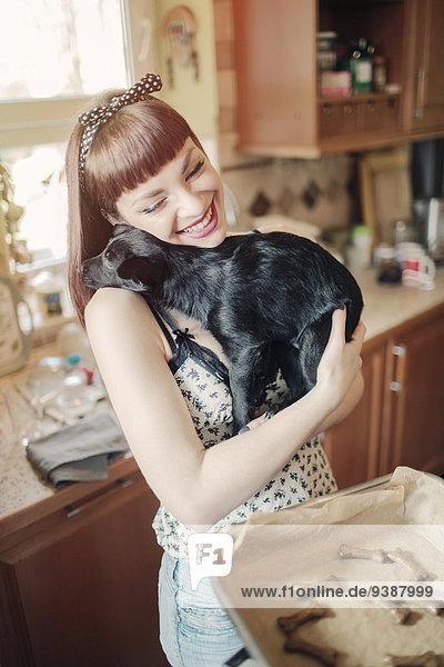 junge Frau junge Frauen umarmen Hund backen backend backt Keks