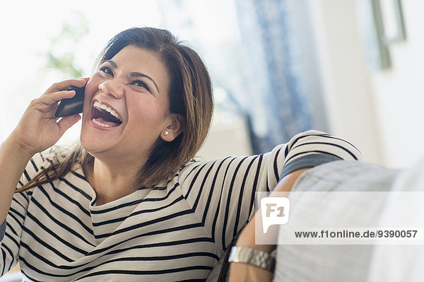 Happy woman sitting on sofa with mobile phone