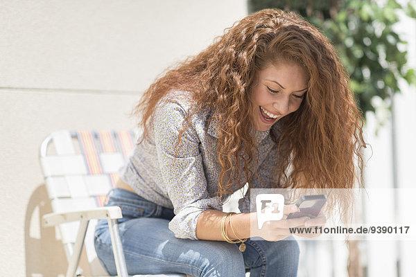 Handy Außenaufnahme sitzend Portrait Frau Stuhl Kurznachricht Terrasse freie Natur