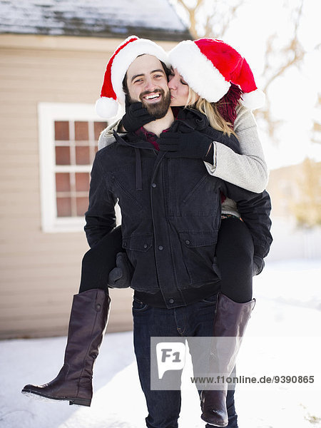 Portrait of young couple in santa hats  piggyback