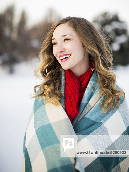 Portrait of woman wrapped in blanket smiling outdoors