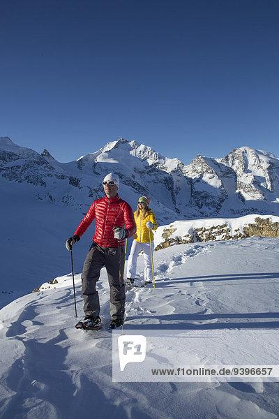 Schneeschuh Frau Winter Mann gehen Weg wandern Kanton Graubünden Wanderweg Schnee Wintersport