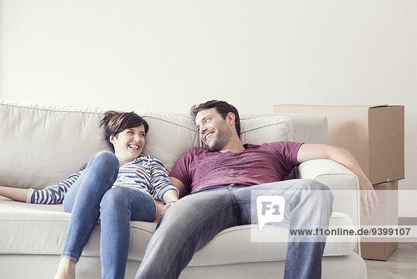 Pärchen beim Umzug auf dem Sofa entspannen