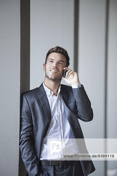 Junger Mann  der sich gegen die Gebäudesäule lehnt und auf dem Handy spricht