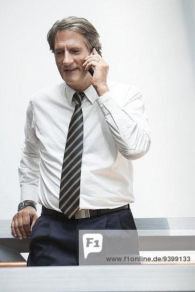 Geschäftsmann lehnt sich gegen das Geländer  spricht am Handy