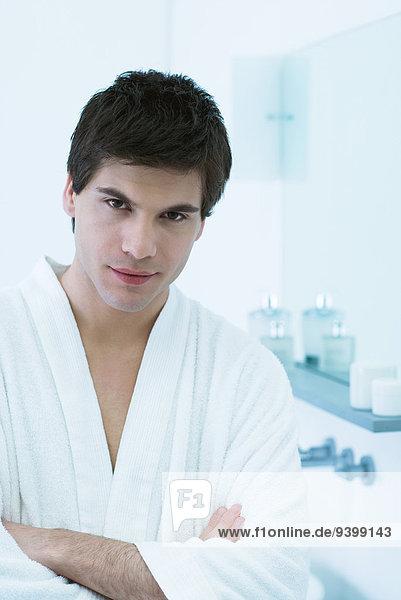 Junger Mann im Bademantel  Arme gefaltet  Portrait