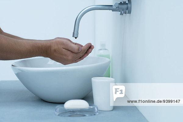Mann hält Hände unter dem tropfenden Wasserhahn im Waschbecken.