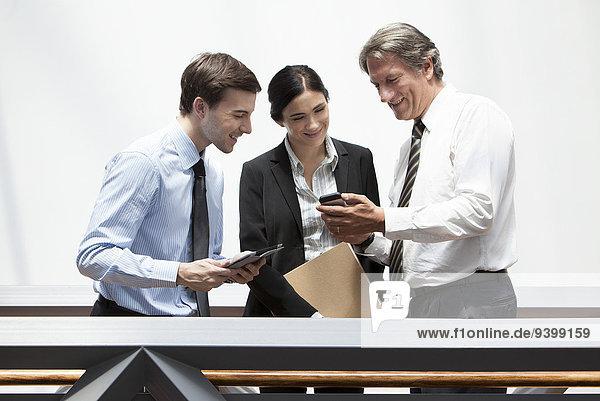 Geschäftsmann zeigt Smartphone den Kollegen