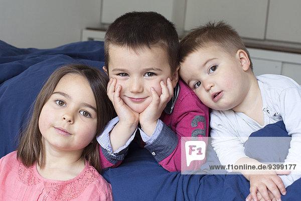 Junge Geschwister entspannen sich gemeinsam auf dem Bett  Portrait