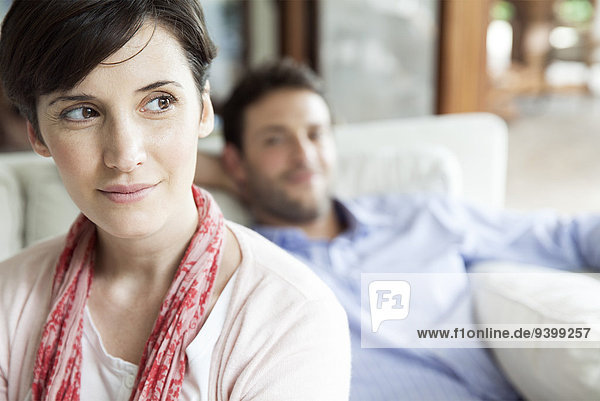 Woman looking away dreamily  man relaxing in background